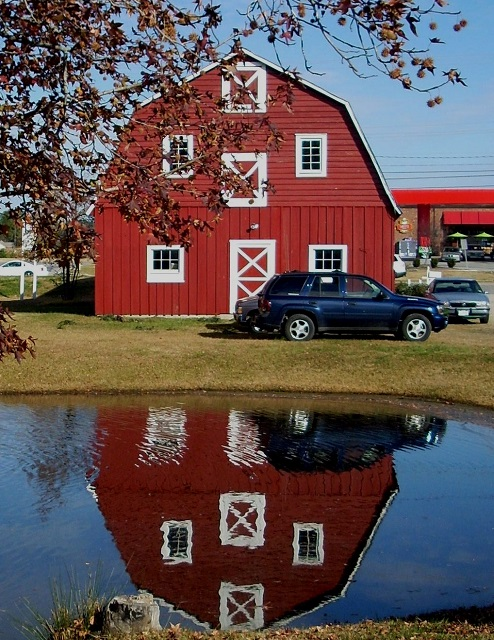 Red barn in pond with blue sky.