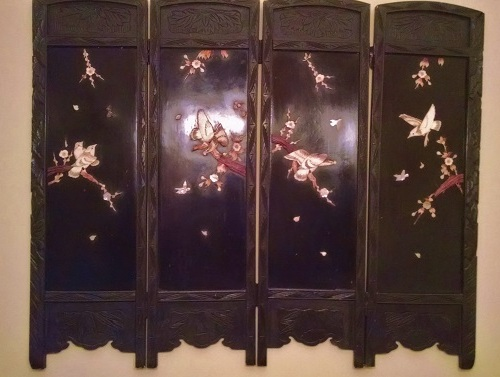 Asian black wood screen with carved images.