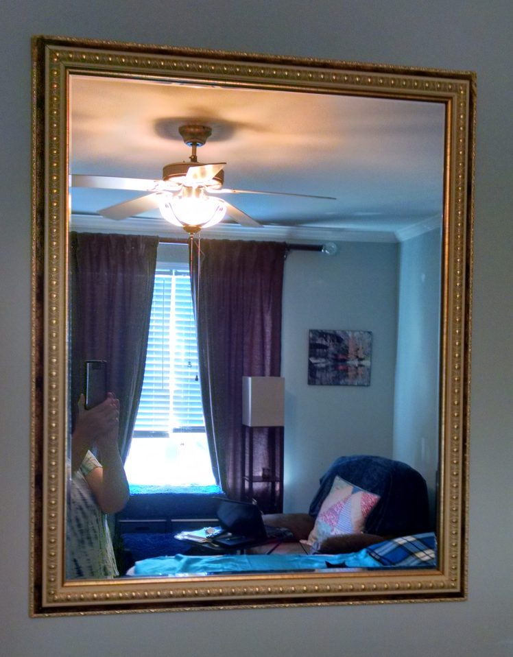 Mirror in the bedroom, reflecting the light of the window.