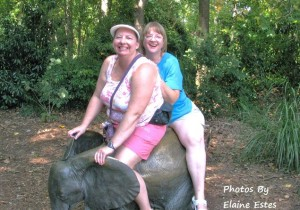 Friends on a baby elephant statue at the zoo