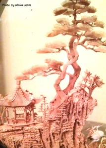 Cork wood carving of bonsai trees on a mountain top.
