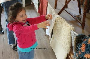 Child smiling as she examines wool.