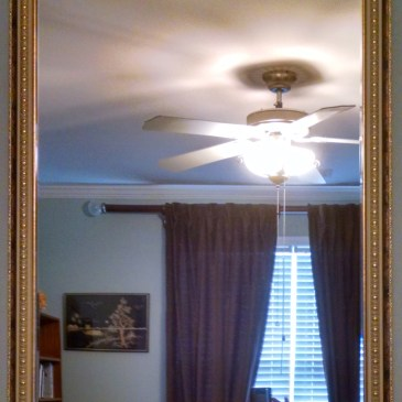 Mirror with gold and white patterned frame.