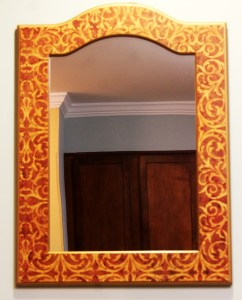 Mirror with lovely pattern on its wooden frame.